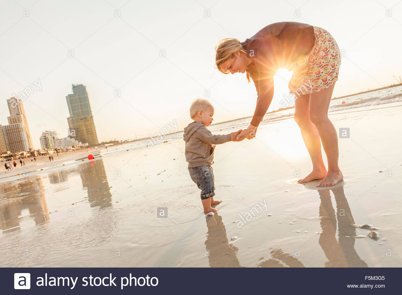 United Arab Emirates, Dubai, Woman with son (12-17 months) on beach at sunset - Stock Image