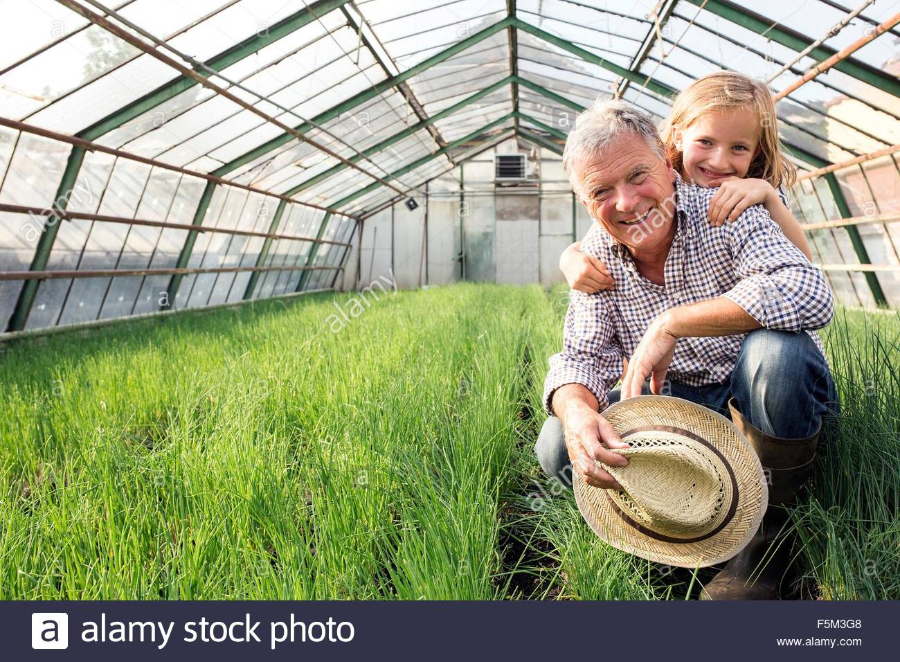 Granddaughter with hands on grandfather shoulders in hothouse full of chives, looking at camera smiling - Stock Image