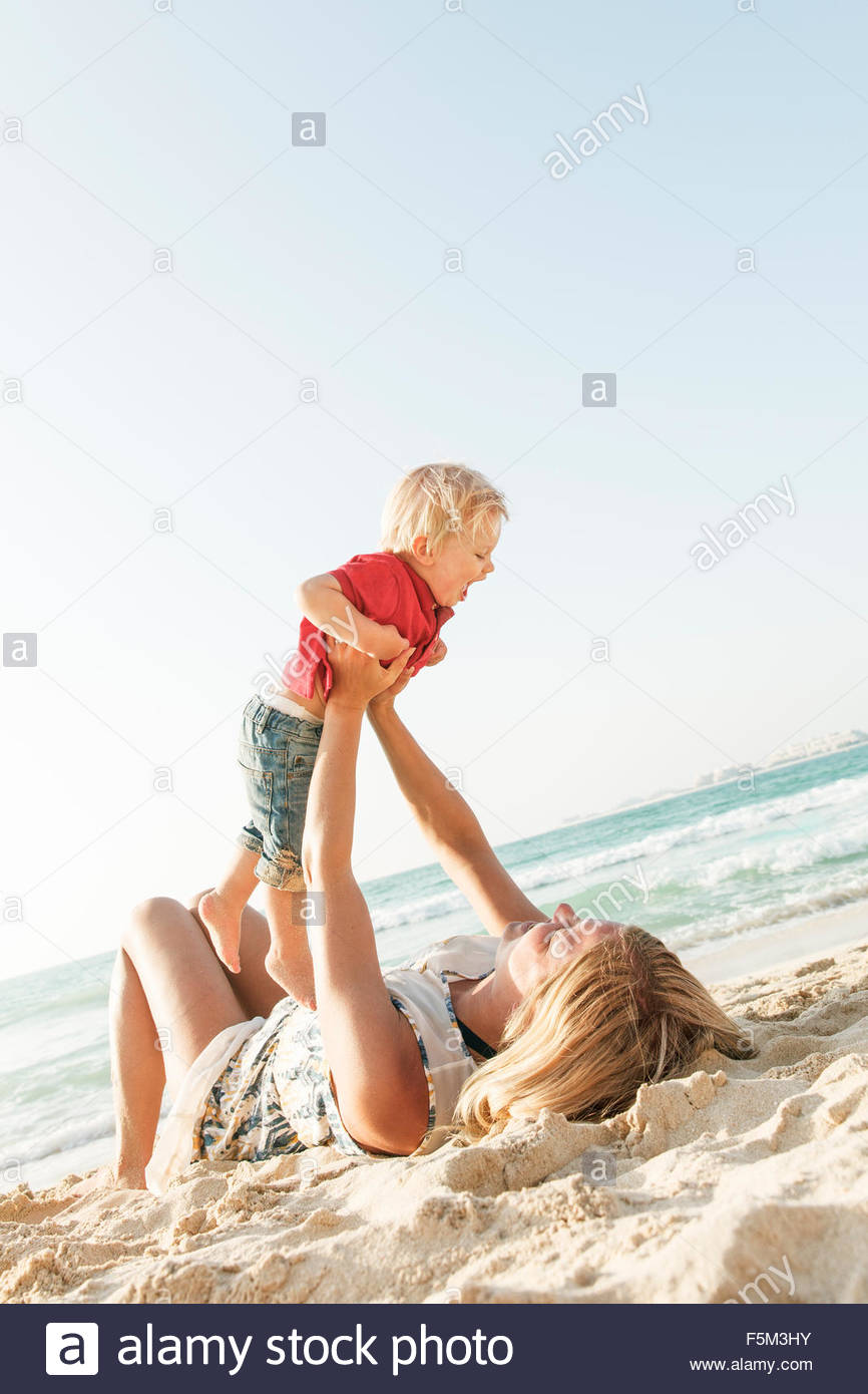 United Arab Emirates, Dubai, Woman with son (12-17 months) on beach - Stock Image