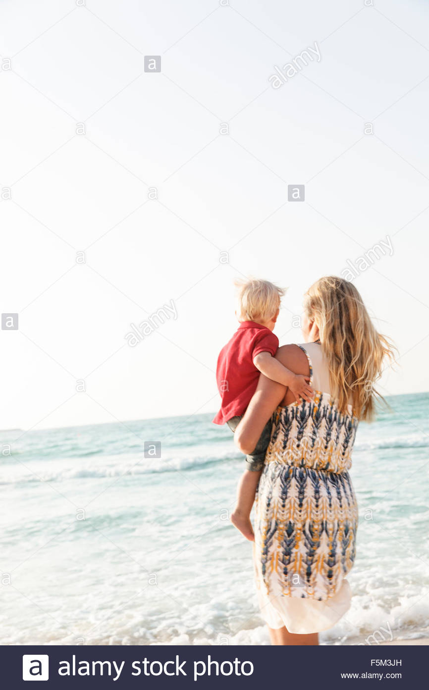 United Arab Emirates, Dubai, Woman carrying son (12-17 months) on beach - Stock Image