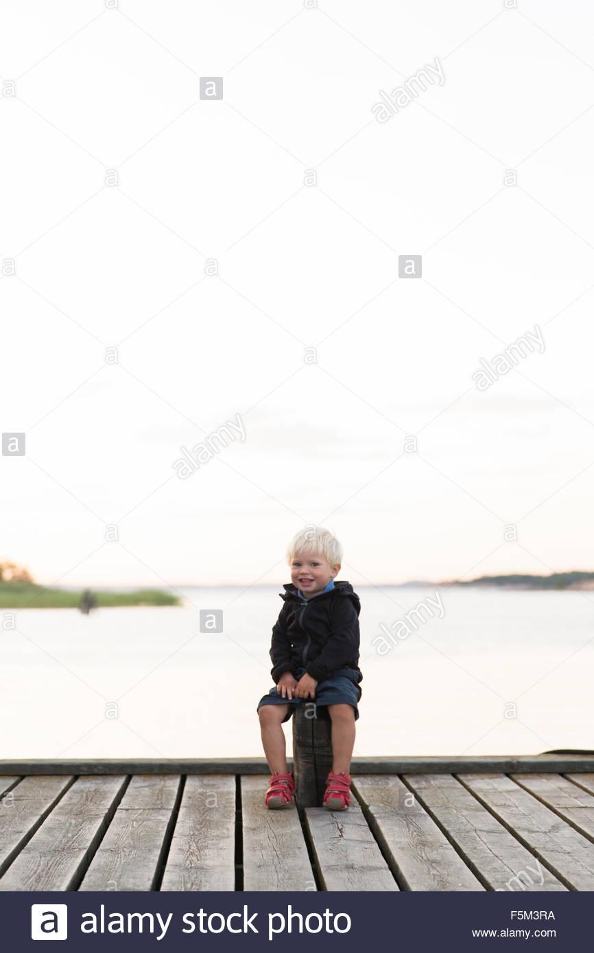 Sweden, Stockholm Archipelago, Sodermanland, Uto, Boy (12-17 months) sitting on jetty - Stock Image