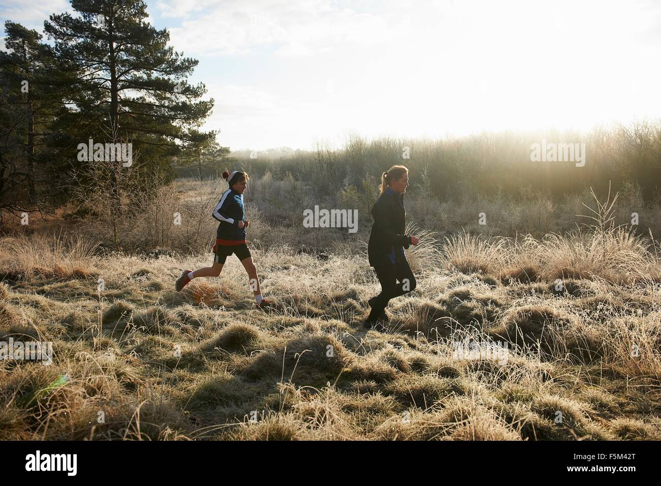 Side view of mother and sons running on frosty grassland - Stock Image