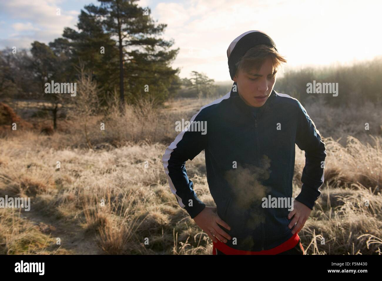 Teenage boy on frosty grassland, visible breath, hands on hips looking down - Stock Image