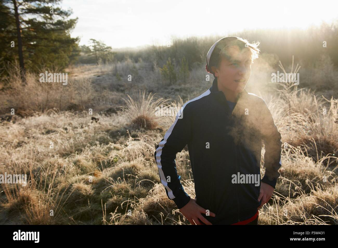 Teenage boy on frosty grassland, visible breath, hands on hips looking away - Stock Image