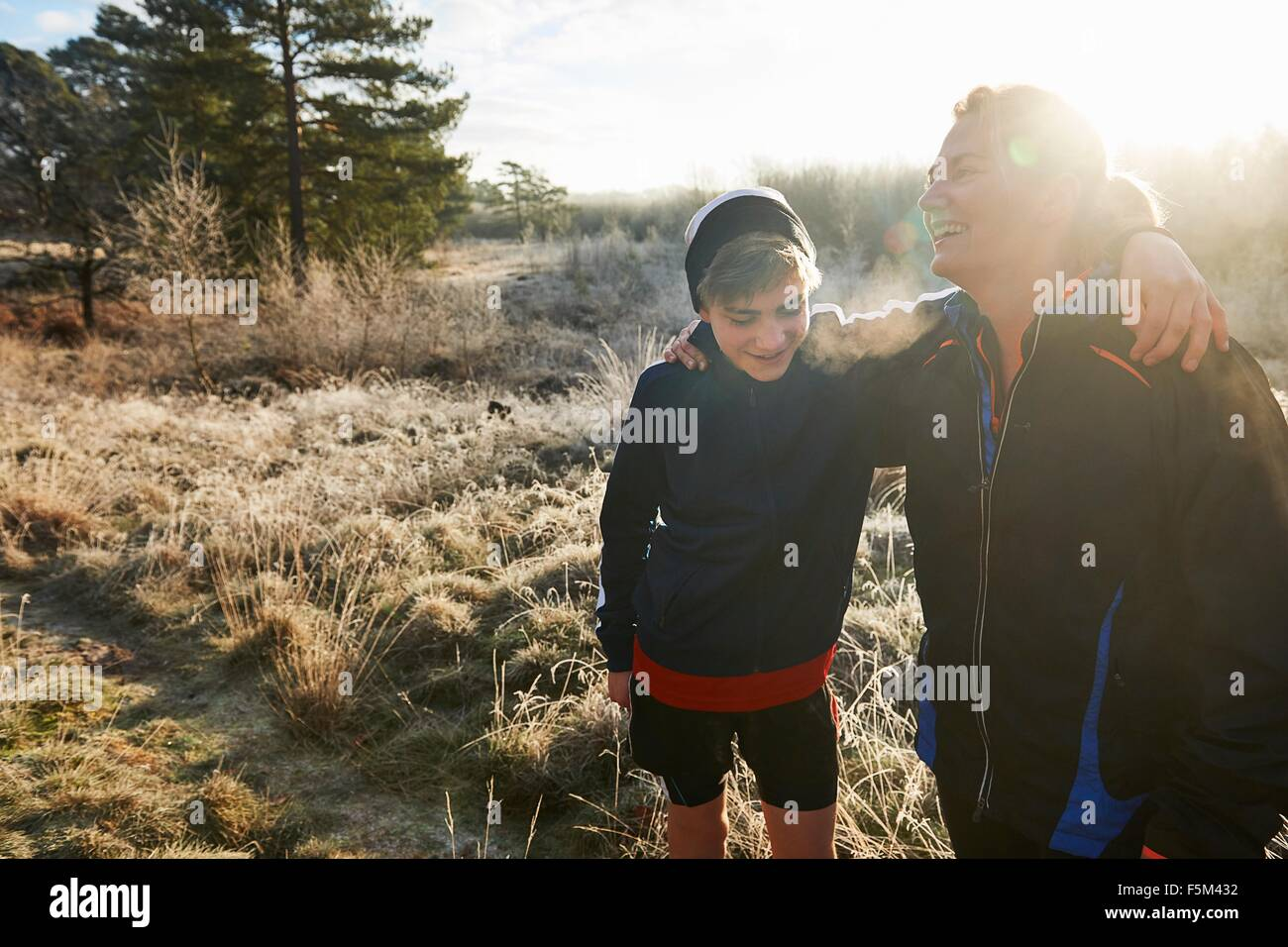 Mother and son on grassland wearing sports clothing arms around each other smiling - Stock Image