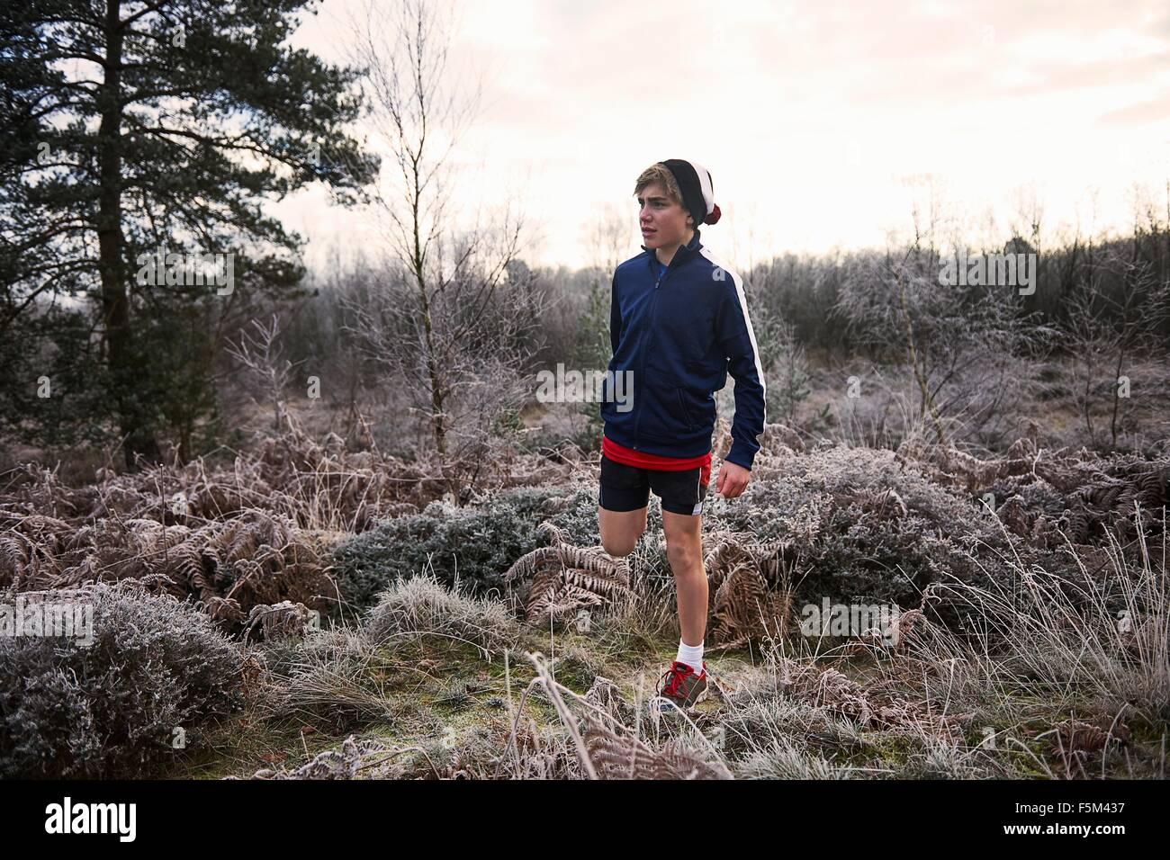 Teenage boy on frosty grassland wearing sportswear stretching leg looking away - Stock Image