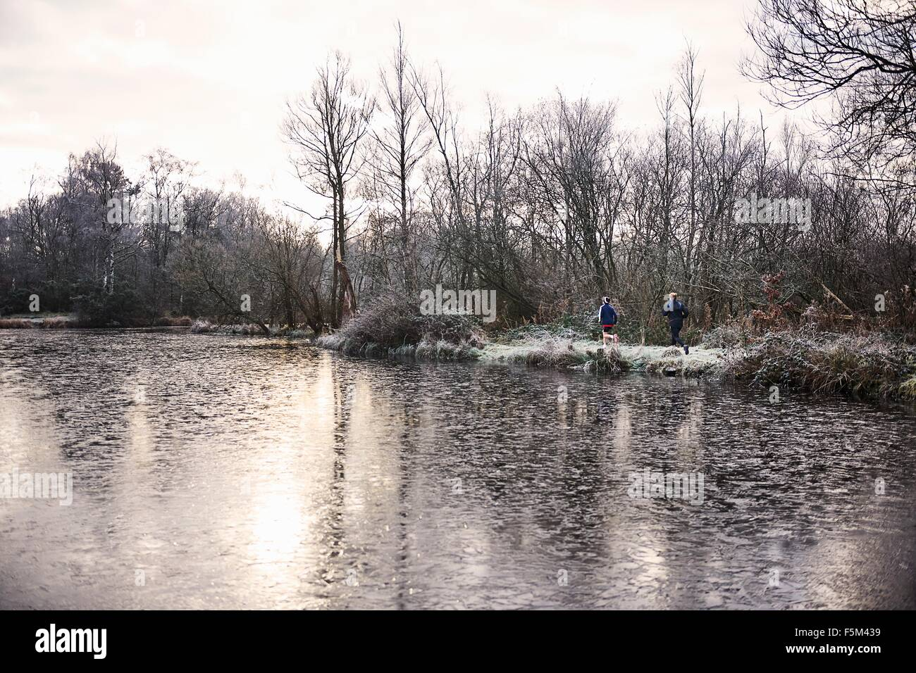 View across icy lake of mother and son running together Stock Photo