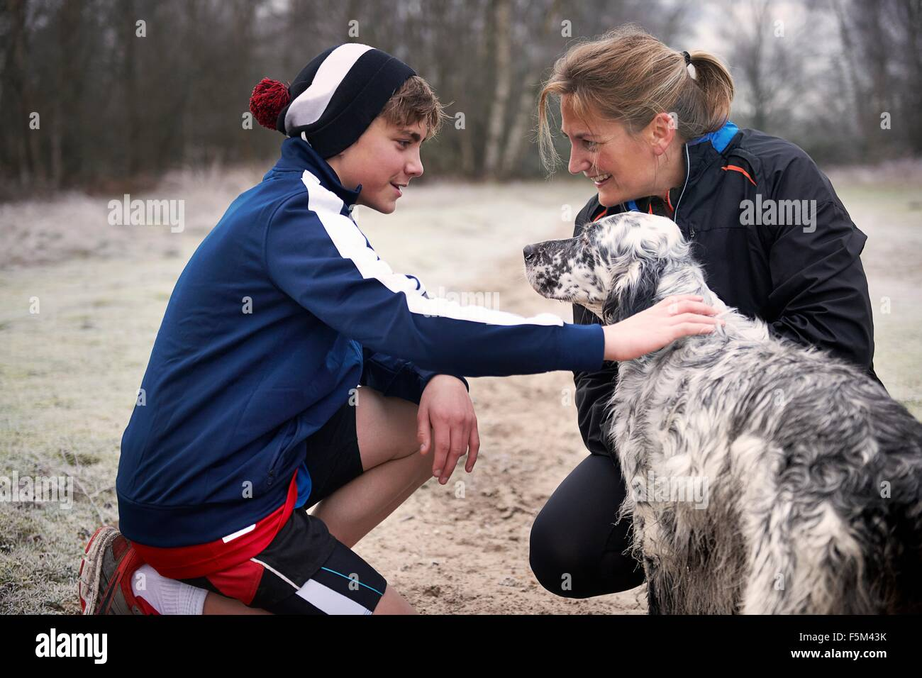 Mother and son crouching down stroking dog, face to face smiling - Stock Image