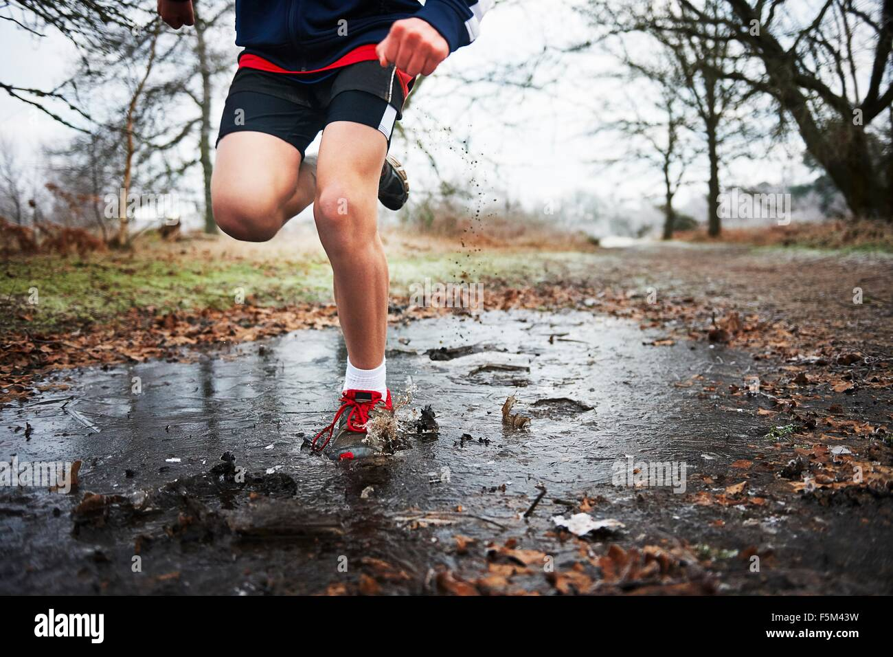 Front view of teenage boy running through puddle - Stock Image