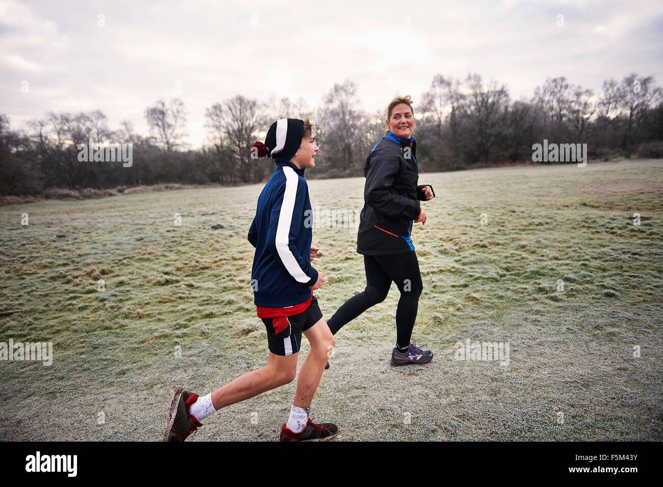 Side view of mother and son running on grassland smiling - Stock Image
