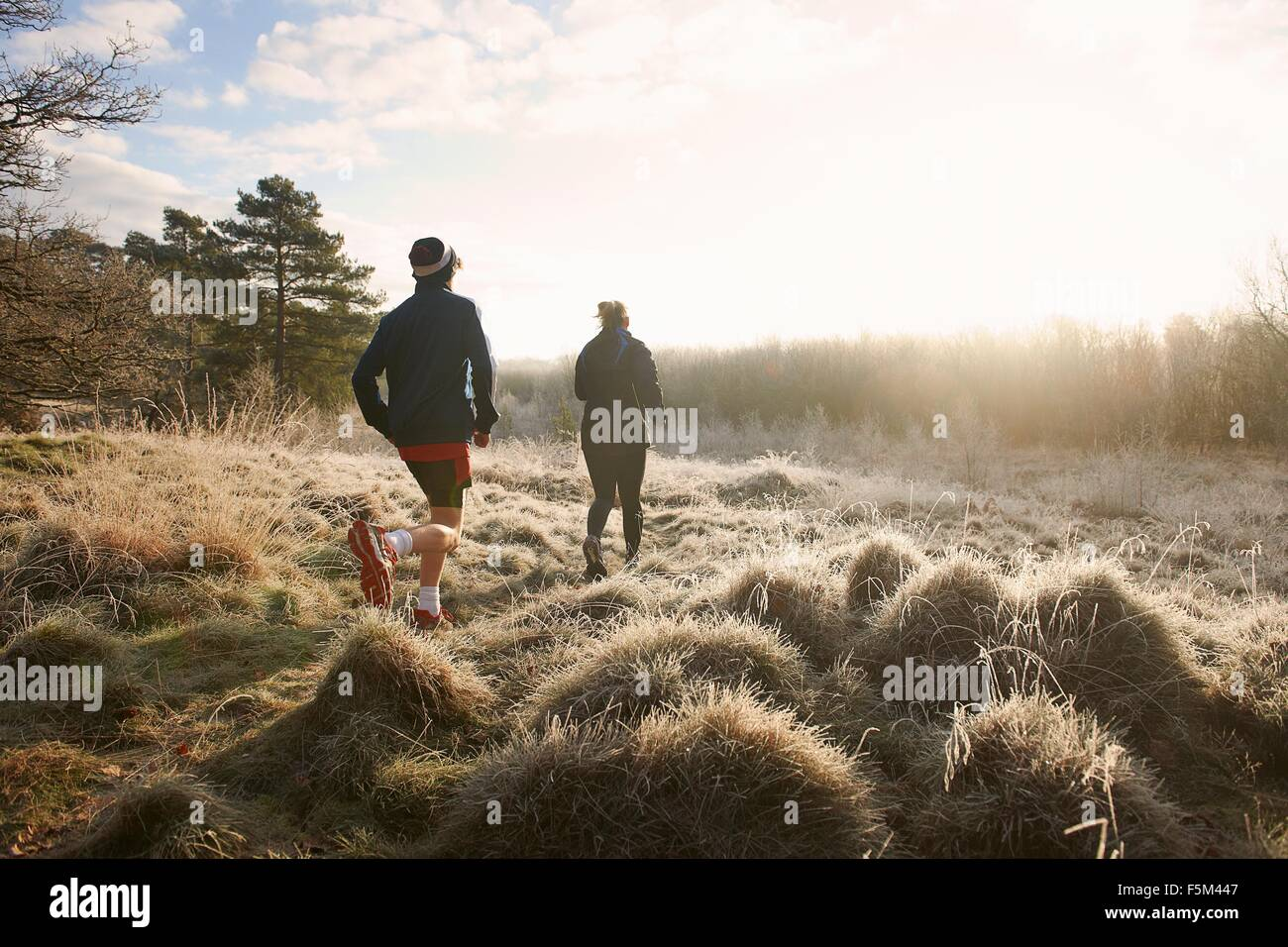 Rear view of mother and son running on grassland - Stock Image