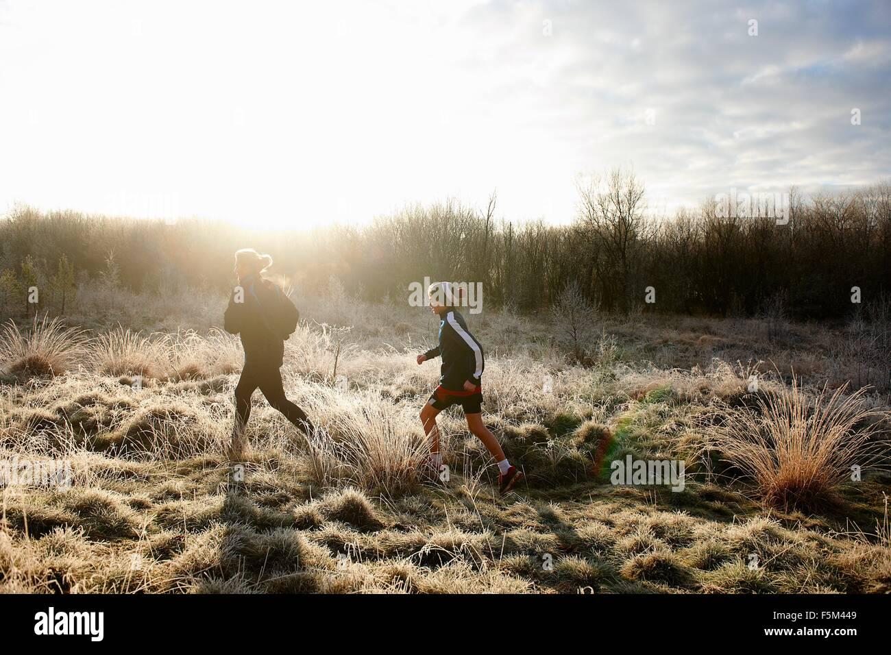 Side view of mother and son running on grassland - Stock Image