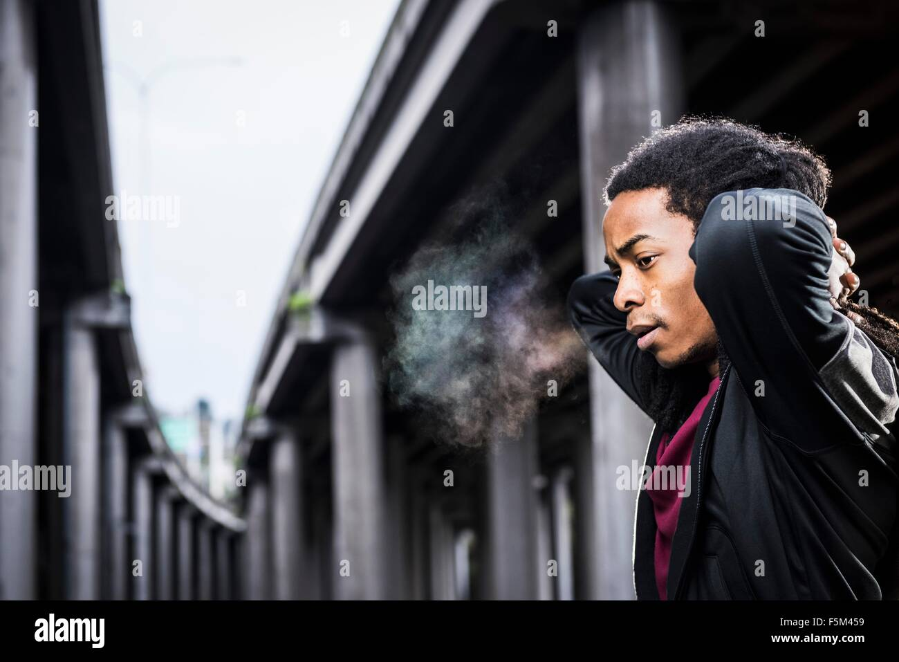 Male boxer with hands behind neck below urban flyover - Stock Image