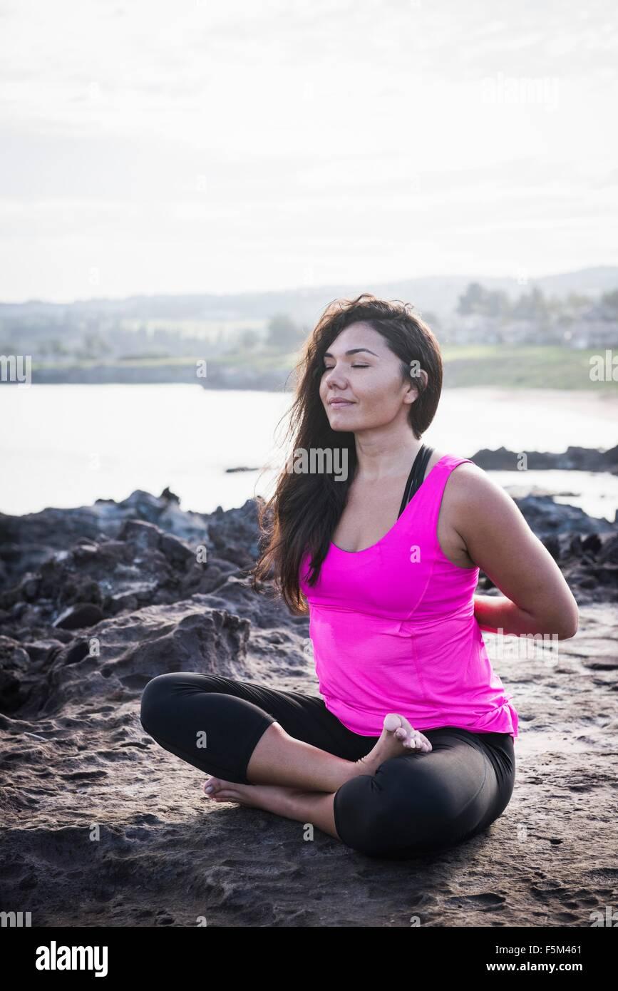 Woman at coast practicing yoga in lotus position, Hawea Point, Maui, Hawaii, USA Stock Photo