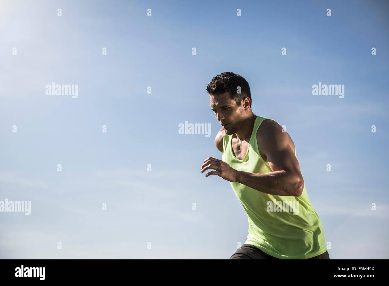 Young man wearing vest running in front of blue sky - Stock Image