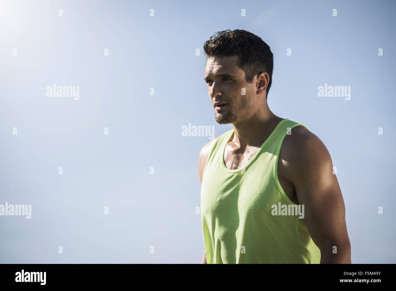 Portrait of confident athletic young man and blue sky - Stock Image