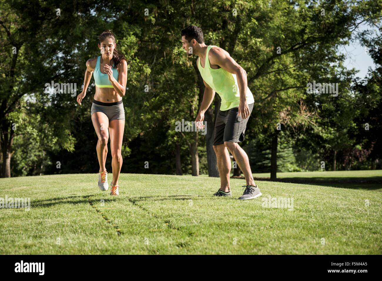 Young woman and teammate training with agility ladder in park - Stock Image