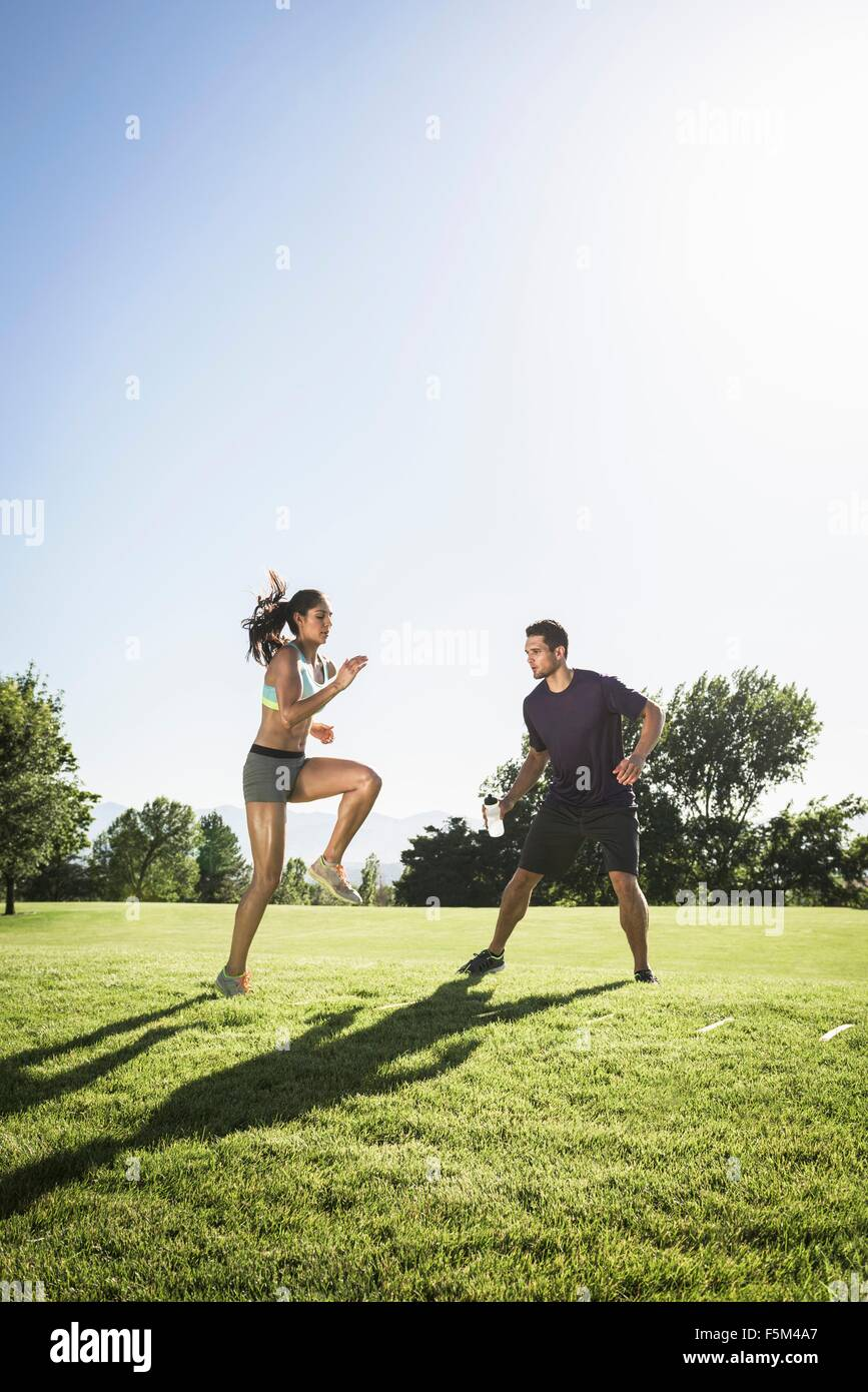 Young woman training with agility ladder in park - Stock Image
