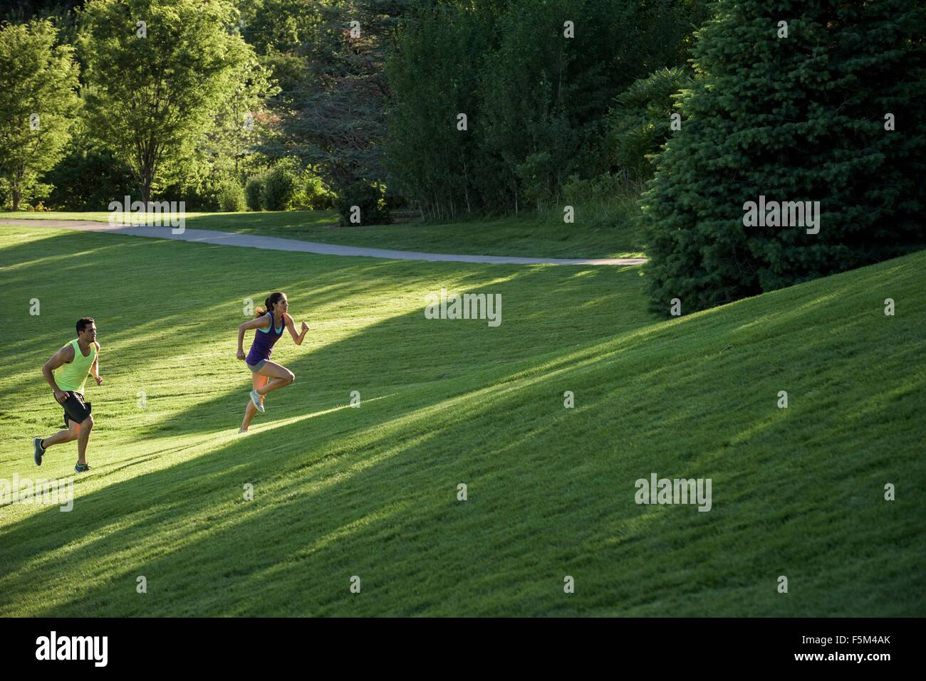 Young man and woman doing training runs on hill in park - Stock Image
