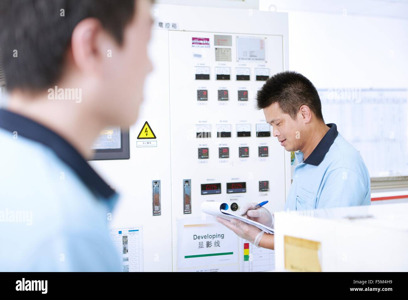 Colleagues at work in flexible electronics plant Stock Photo