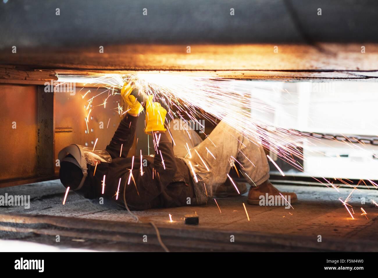 Welder welding beneath boat in shipyard workshop - Stock Image
