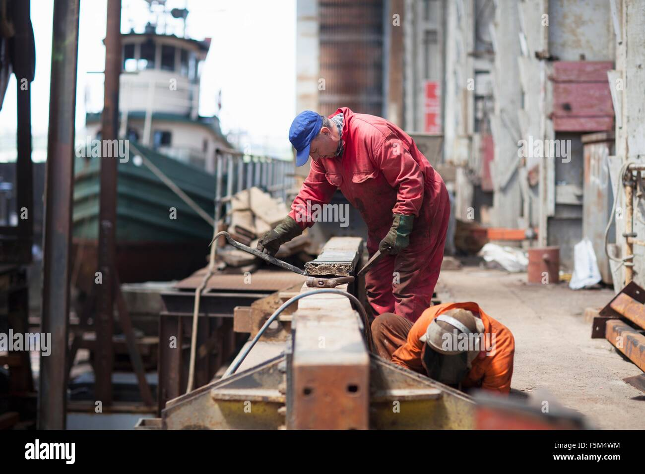 Workers doing maintenance in shipyard workshop - Stock Image