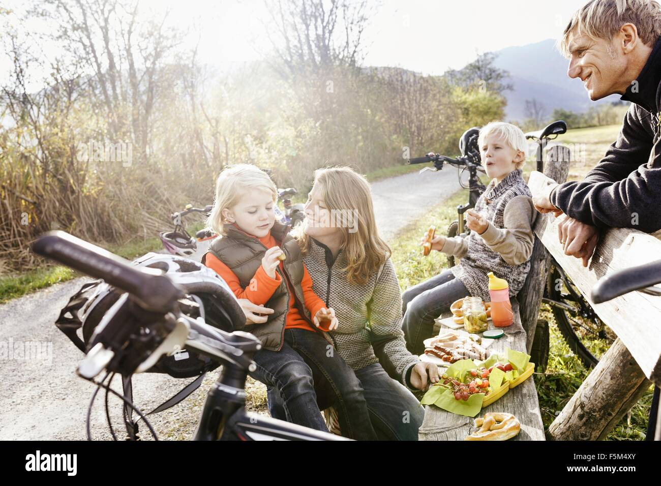 Family with bicycles resting on bench by roadside eating picnic smiling - Stock Image
