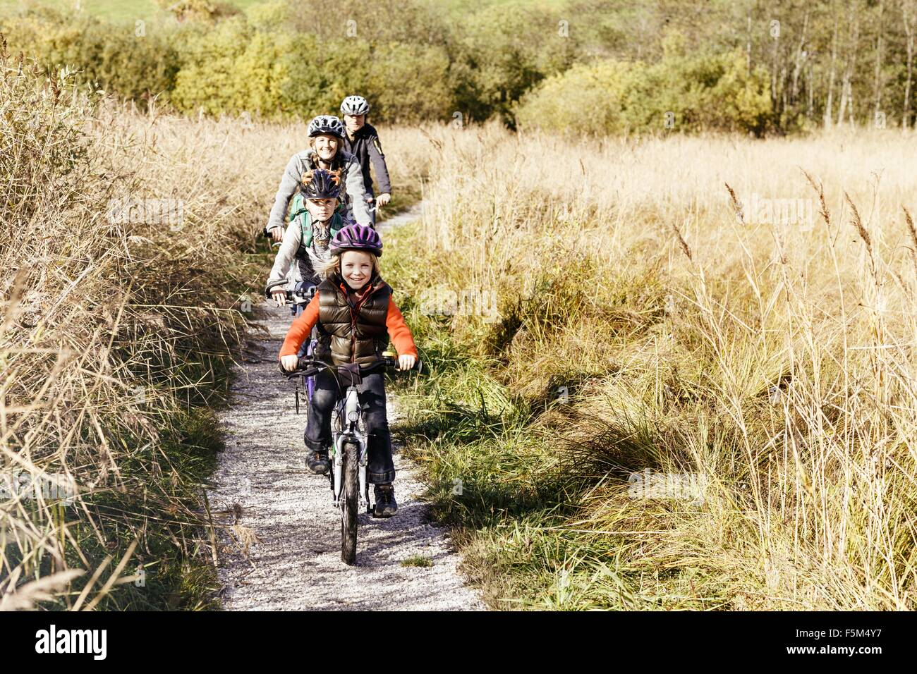 Front view of family cycling on rural path looking at camera smiling Stock Photo