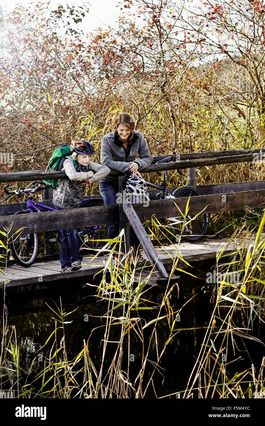 Mother and son with bicycles standing on wood footbridge looking down at river Stock Photo