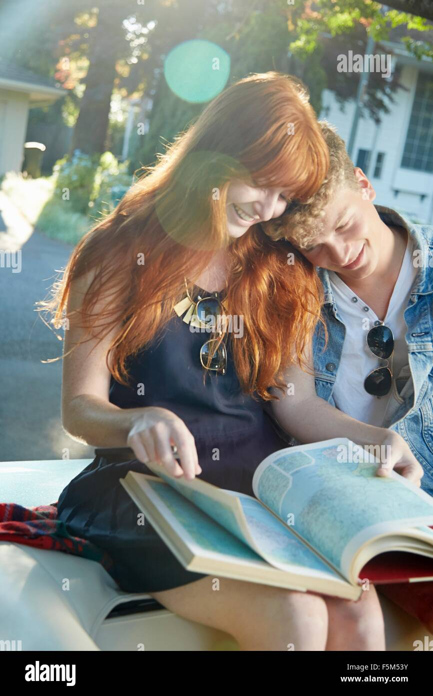 Young couple in vintage convertible reading road atlas Stock Photo