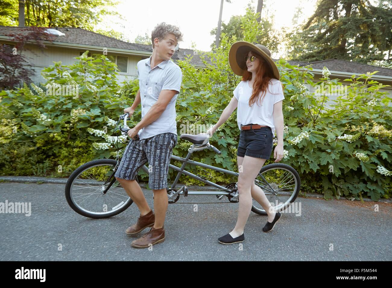 Young couple on suburban road preparing for tandem cycle ride - Stock Image