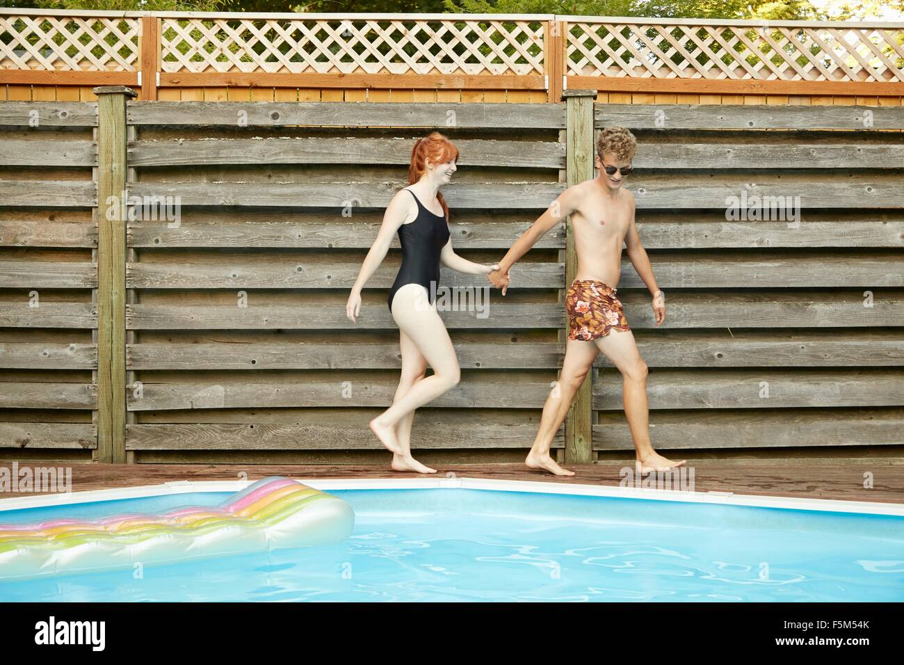Young couple wearing swimwear holding hands on poolside - Stock Image