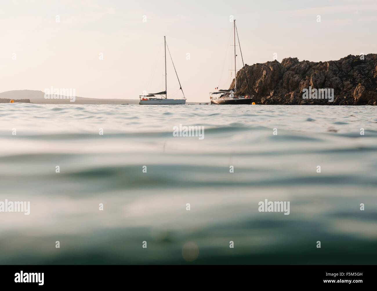 Surface level view of two yachts anchored at sea, Menorca, Balearic islands, Spain - Stock Image