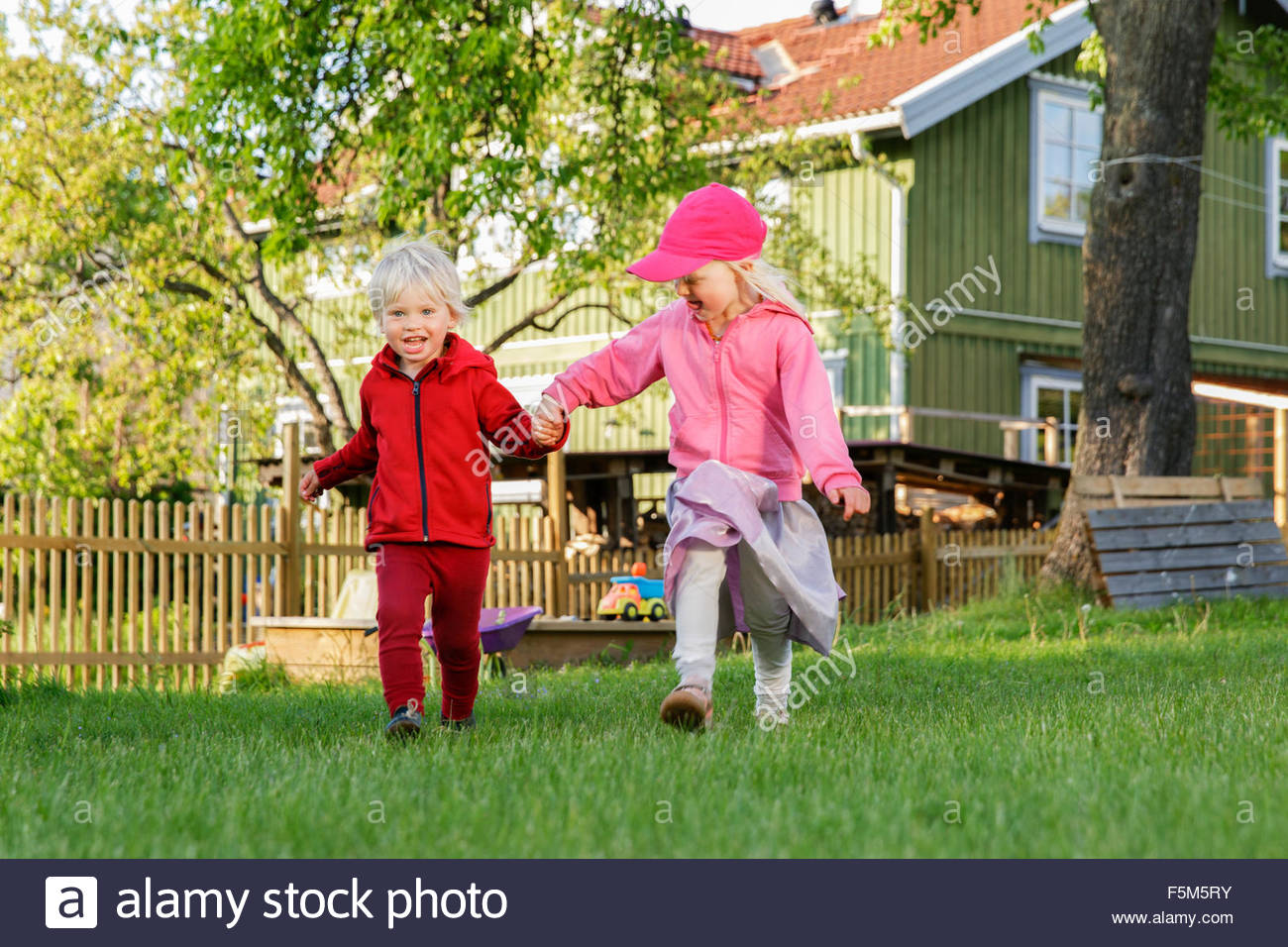 Sweden, Sodermanland, Jarna, Children (2-3, 4-5) playing on front yard - Stock Image