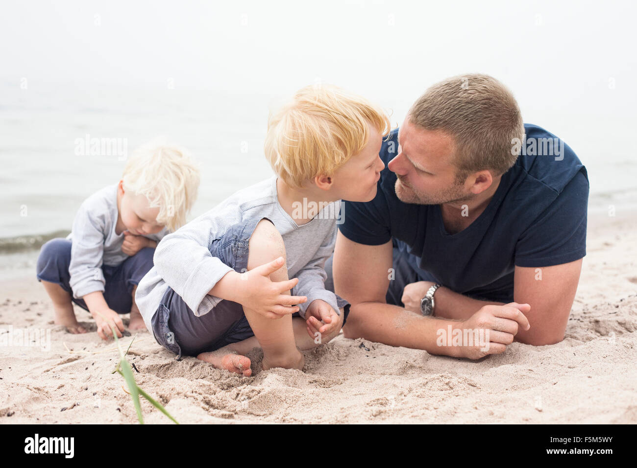 Sweden, Gotland, Ljugarn, Two boys (2-3, 4-5) spending time with man on beach - Stock Image