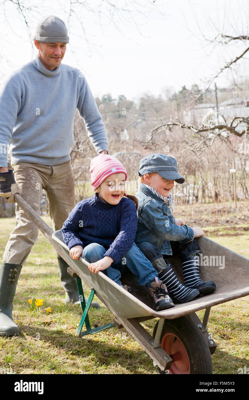 Sweden, Sodermanland, Huddinge, Stuvsta, Father with sons (4-5) in wheelbarrow - Stock Image