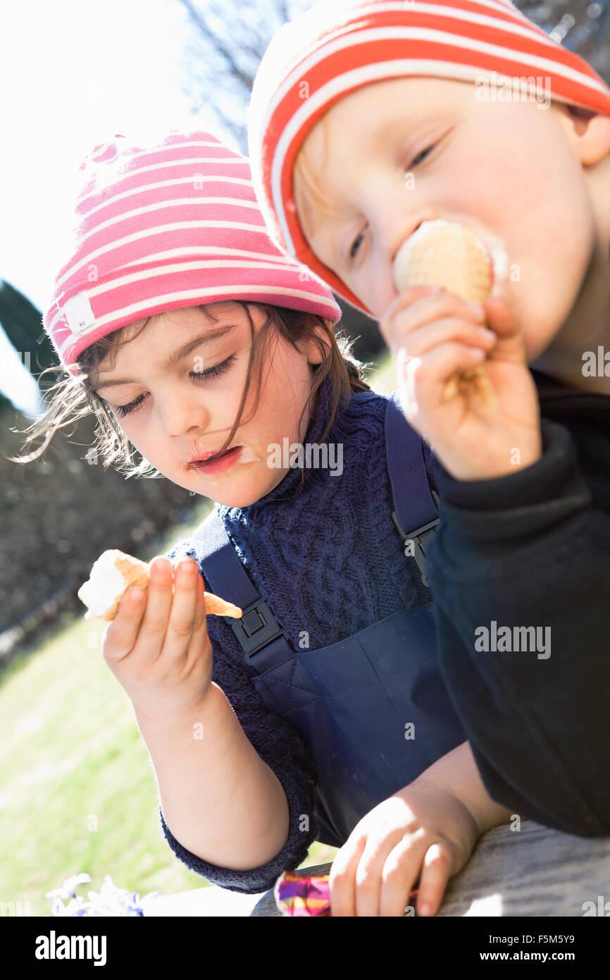 Sweden, Sodermanland, Alvsjo, Children (4-5) eating ice creams - Stock Image