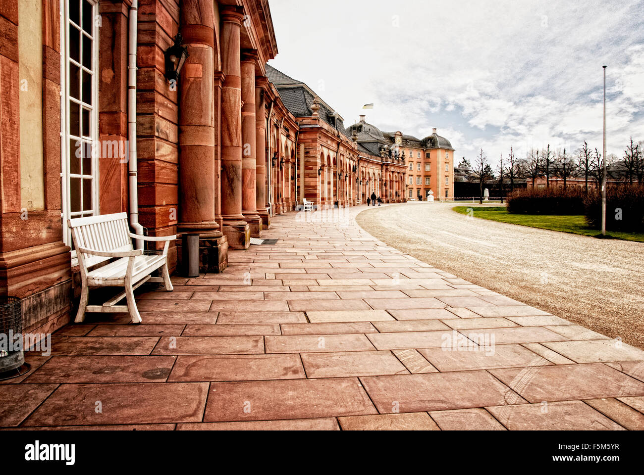 Red sandstone palace walkway with row of smooth columns. - Stock Image