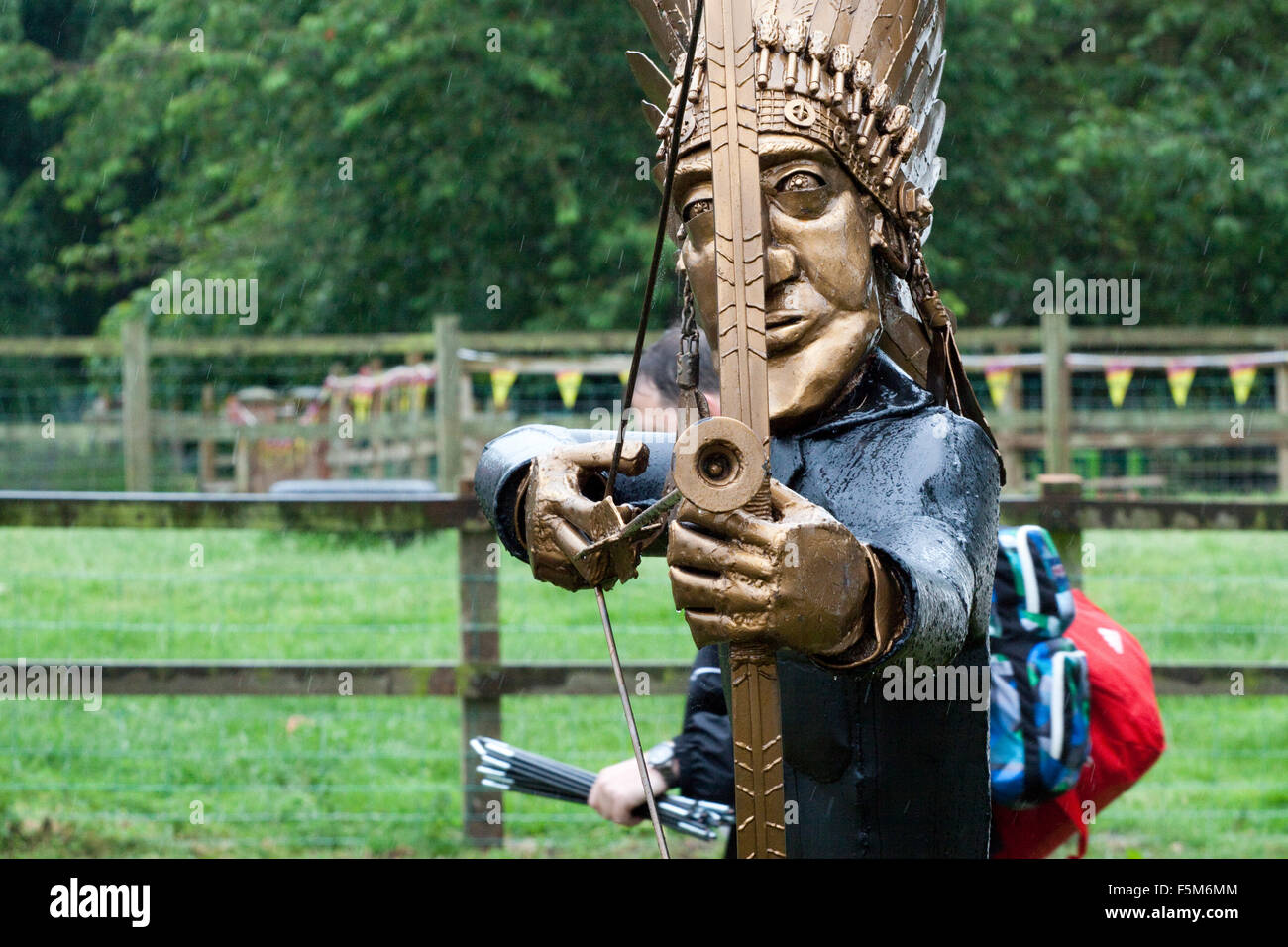 Sculpture of a native American drawing a bow at the camera - Stock Image