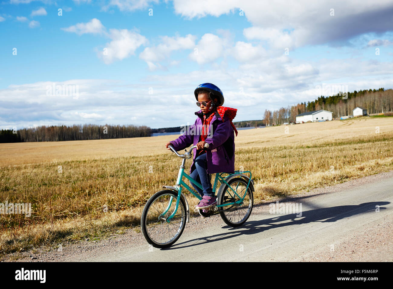 Sweden, Vastra Gotaland, Gullspang, Runnas, Girl (6-7) cycling in countryside Stock Photo