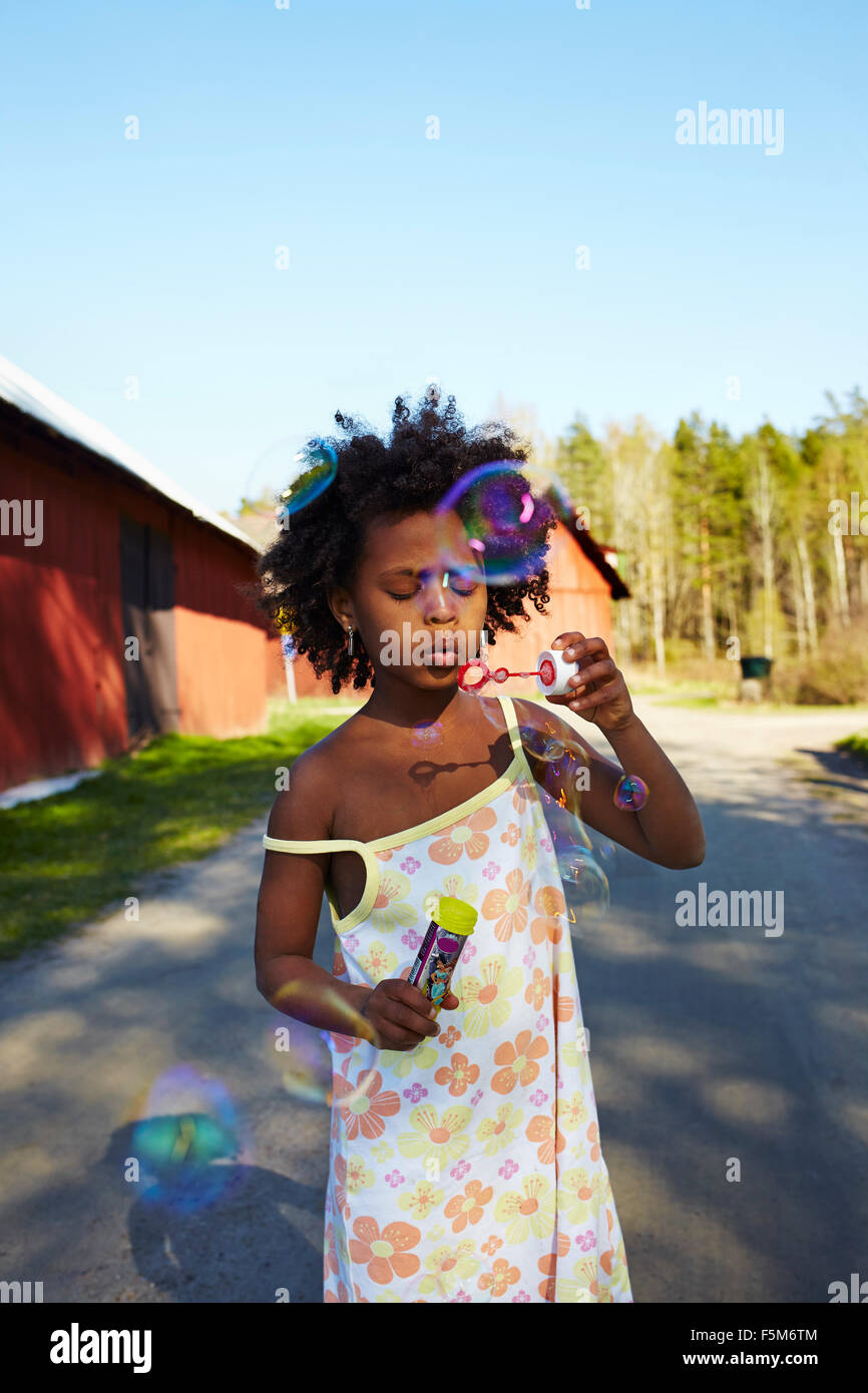 Sweden, Vastra Gotaland, Gullspang, Runnas, Girl (6-7) blowing soap bubbles Stock Photo