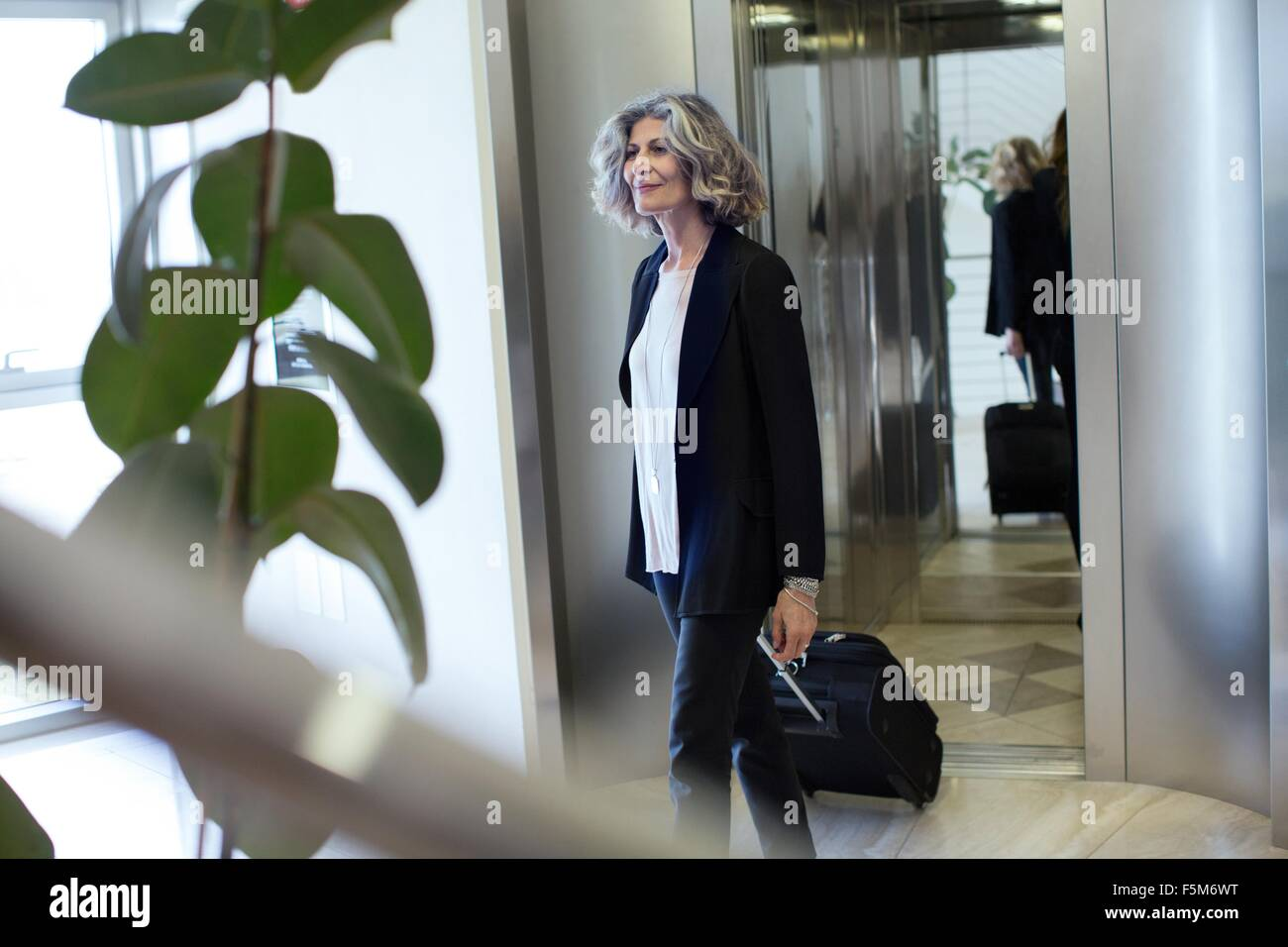 Senior businesswoman with wheeled suitcase in office building - Stock Image