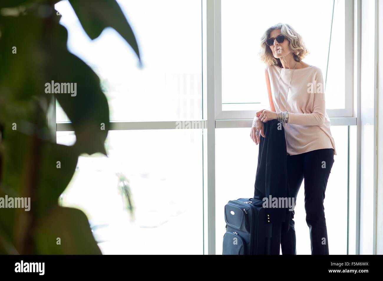 Senior businesswoman waiting with wheeled suitcase in office building - Stock Image
