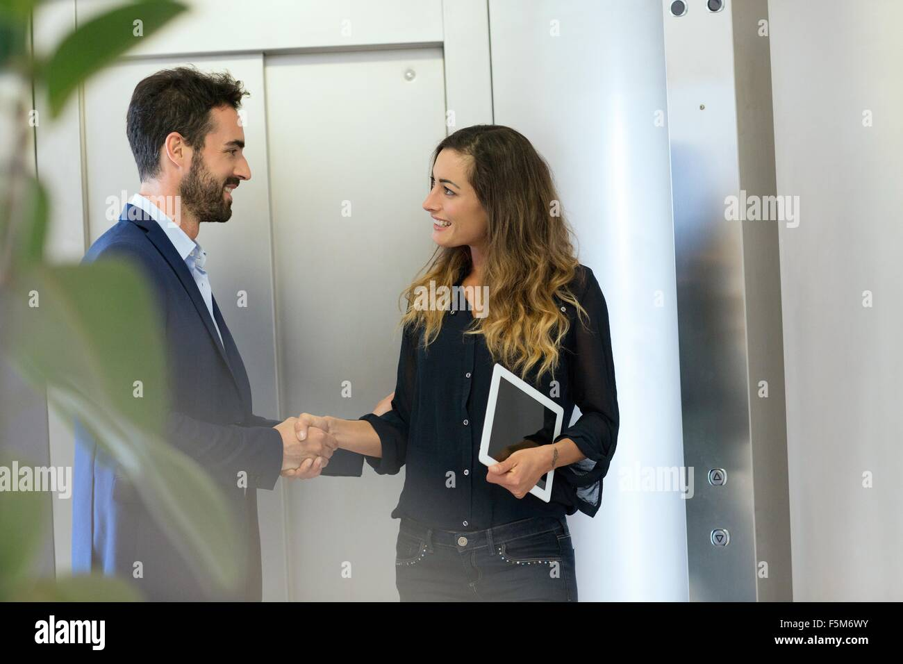 Young businessman and woman shaking hands at elevator - Stock Image