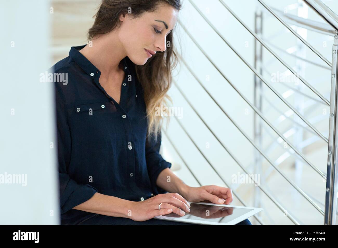 Young businesswoman using digital tablet on office stairway - Stock Image