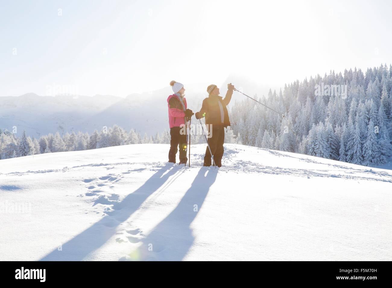 Senior couple on snow covered landscape holding walking poles looking away, Sattelbergalm, Tyrol, Austria - Stock Image