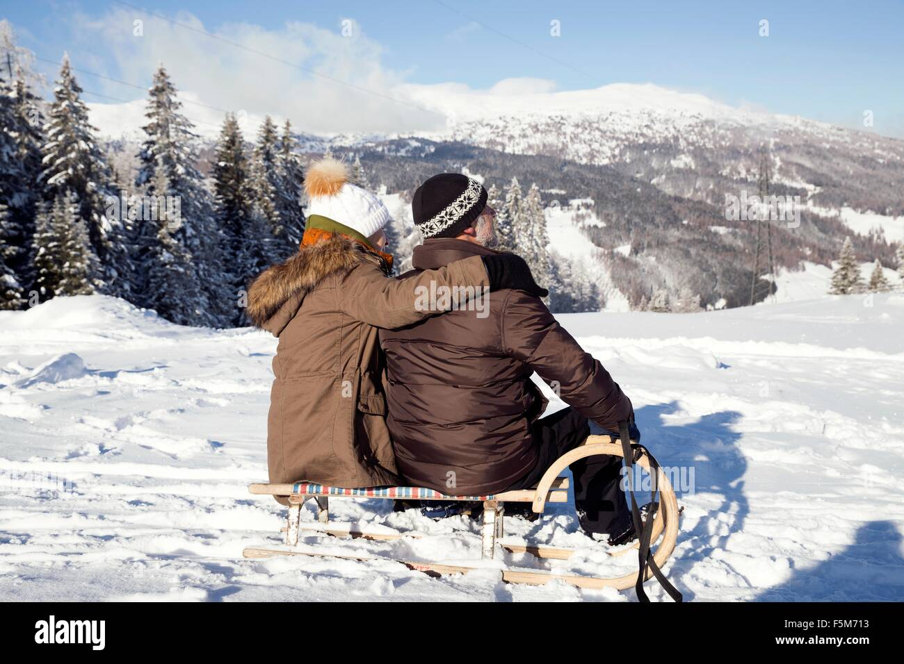 Snow capped mountains and rear view of senior couple sitting on sledge looking away, Sattelbergalm, Tyrol, Austria - Stock Image