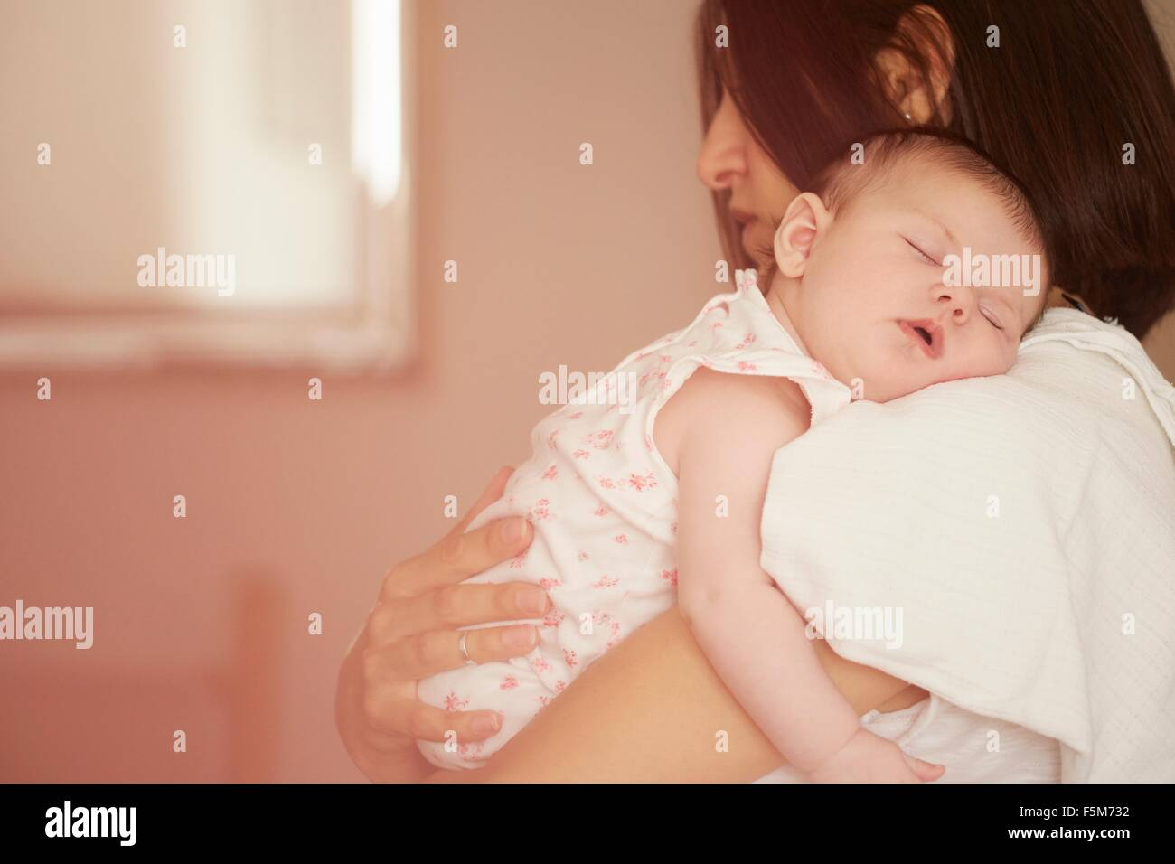 Mother carrying sleeping baby - Stock Image