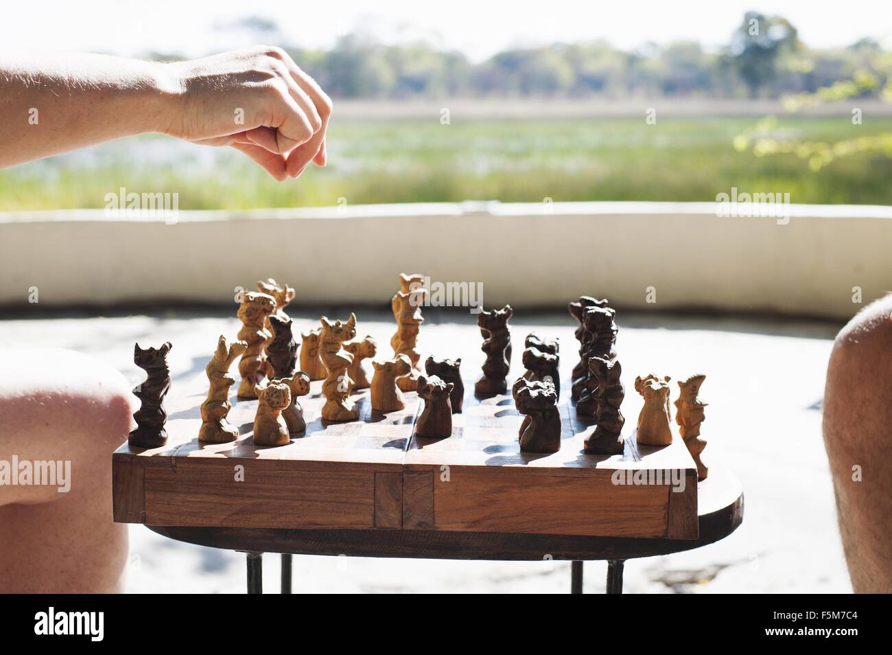 Cropped shot of woman and man playing chess at safari lodge, Kafue National Park, Zambia - Stock Image
