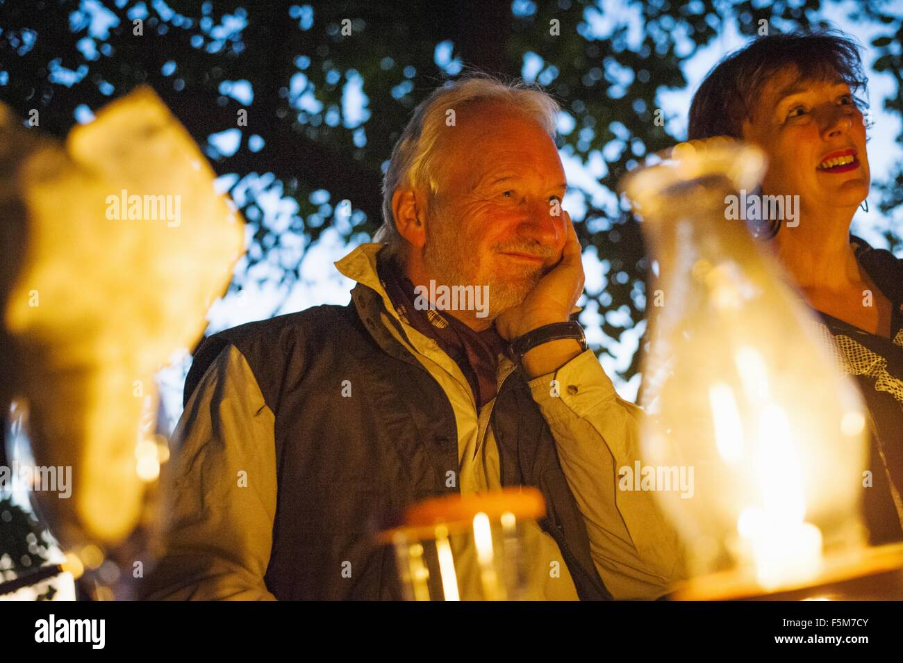 Couple relaxing at dinner table at safari lodge, Kafue National Park, Zambia - Stock Image